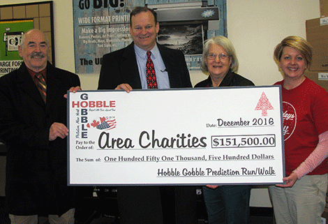 The 19th Hobble Gobble raised $14,000 for local charities. The amount on the novelty check is their total throughout the event's 19 years. Above, race director Derry Loucks, William Marilleyv from Excellus BlueCross BlueShield, Pamela Yugartis from the Potsdam Holiday Fund and assistant race director Janice Adderley.
