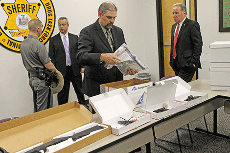 Det. Arthur Shattuck, St. Lawrence County Sheriff's Office, displays confiscated guns and drugs.