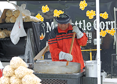 A vendor at the Mr. Kettle Corn stand makes kettle corn.