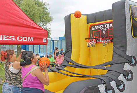Dawn Benedict and Kaiennahawi of Akwesasne shoot hoops at the U.S. Army display.