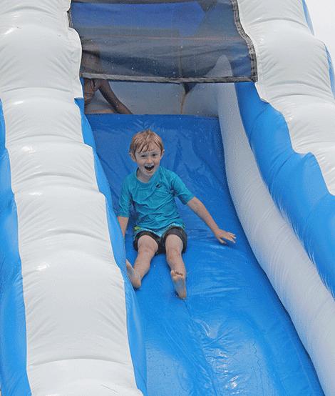 Cooper Backus-Mackey of Waddington takes a ride on a water slide.