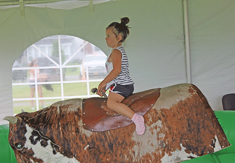 Reagan Richards of Massena rides a mechanical bull built into an inflatable ring.