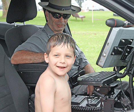 Tpr. James D'Ambro from the Ray Brook station shows the inside of a state police cruiser to Hunter Spriggs of Lisbon.