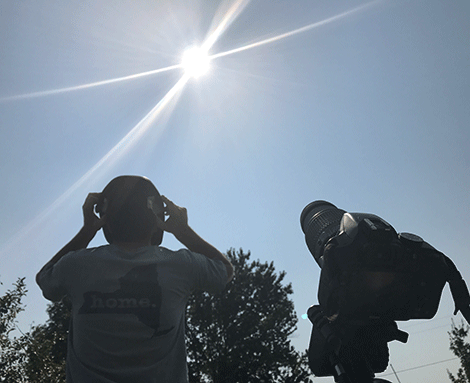 Levi Zufall looks through a welding mask to view the eclipse Monday afternoon on the Zufall farm in Lisbon.