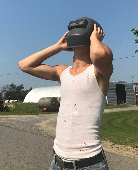 The entire Zufall Family in Lisbon stopped in the middle of hay making to witness the eclipse through welding masks. Photos all taken by David Zufall. John Zufall holds up a welding mask to view the Eclipse.