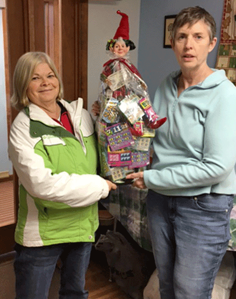 Norwood resident Jeanette Gravelle, left, won Lucky the Elf and his bag of raffle tickets. She is with Friends president Rose Orologio.