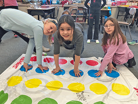 Olivia Plonka, Alexis Herbstler and Aiyana Gaines play Twister in Cheryl Shumway's class.