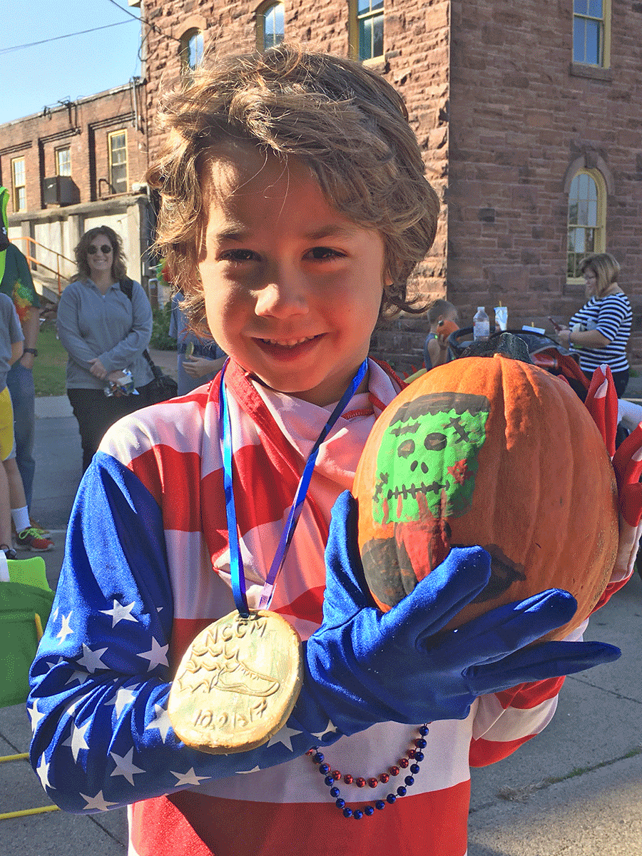Luke Parker holds his prize pumpkin, wearing his handmade first place medal, which he won in the Family Fun Costume Run in Potsdam.
