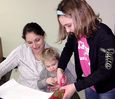 Alecia VanWagner and daughters Lydia, left, and Julia volunteer to wrap gifts for the Potsdam Holiday Fund.