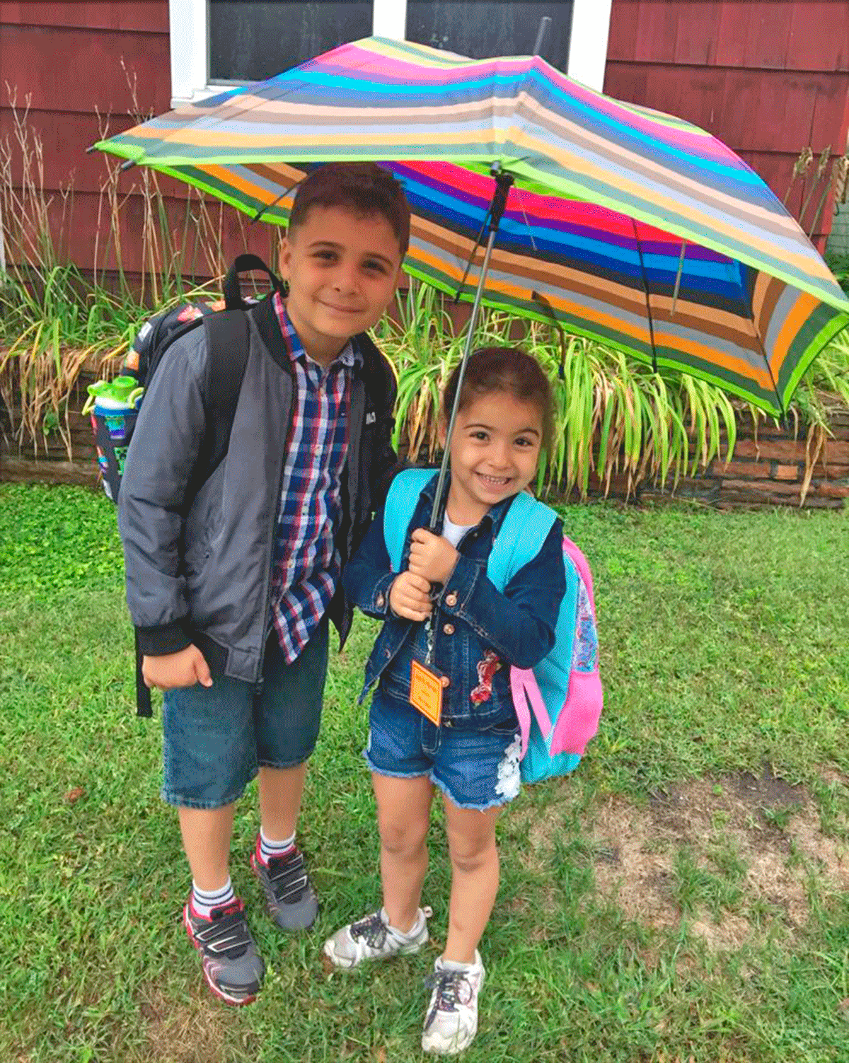Second grader, Matar Almomani, and his sister Jood, kindergartener,  stay dry under their umbrella before starting their first day of school at Potsdam Central School. Submitted photo by Heba Almomani.