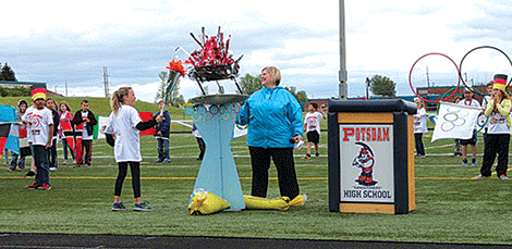 Lawrence Avenue Principal Jennifer Gray helps light the Olympic torch during the school's Olympics opening ceremony.