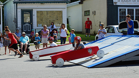Racers in the Go-Kart Derby Race come off the ramps at top speed down Main Street.