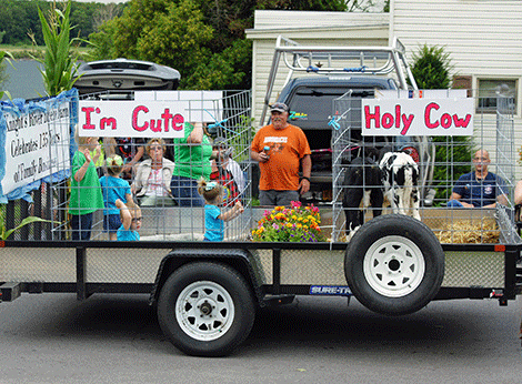 Knight's River Breeze Farm featured a farm-themed parade float celebrating their 135 years in business, complete with cows.