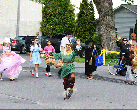 """The Scarecrow lead other """"Wizard of Oz"""" characters down Main Street during the parade."""