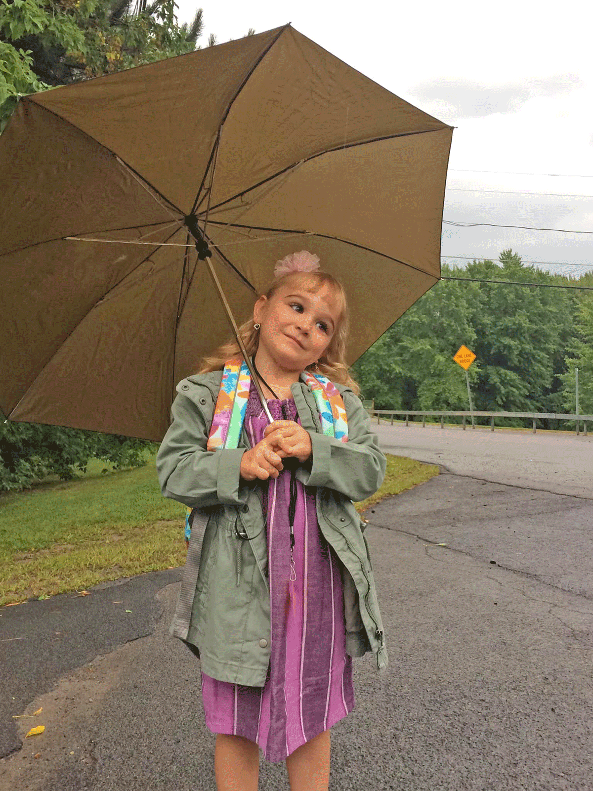 Hosanna Deon, 5, West Stockholm, waits in the rain for her first day of kindergarten at Lawrence Avenue Elementary School in Potsdam. Photo by her father, Chris Deon.