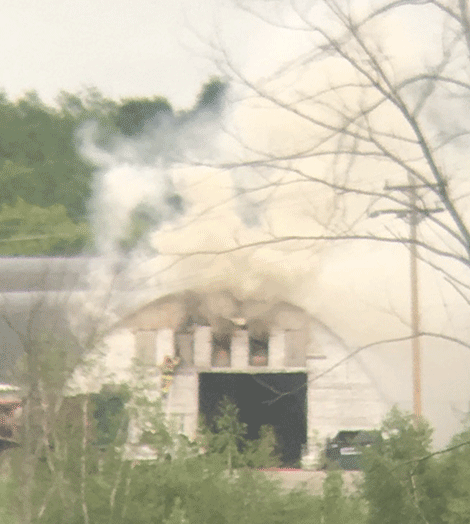 A firefighter climbs a ladder while trying to extinguish the blaze.