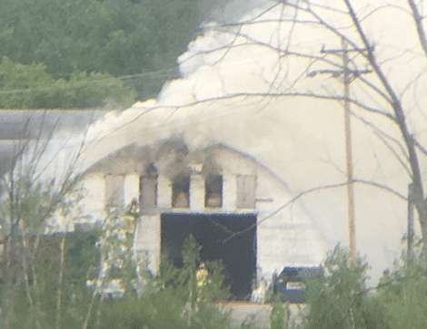 Firefighters work to put out a fire at a building on U.S. Highway 11.