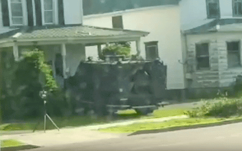 A militarized state police BearCat with a battering ram breaks down the door at 72 Maple St. in Massena during Thursday morning's raid.