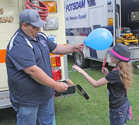 Kayleigh Kenyon-Larmore of Hannawa Falls gets a balloon from a member of the Potsdam Rescue Squad at the group's ice cream social in Ives Park on Thursday.