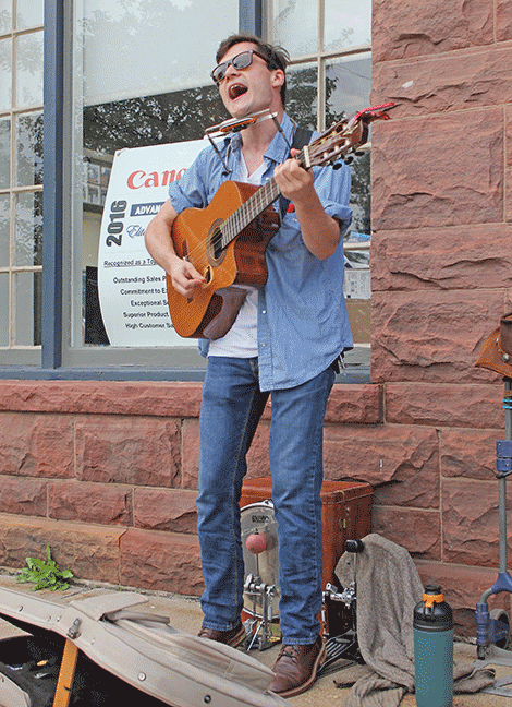 Jackson Cavalier of Norfolk busks at the corner of Market and Main streets on Thursday evening.