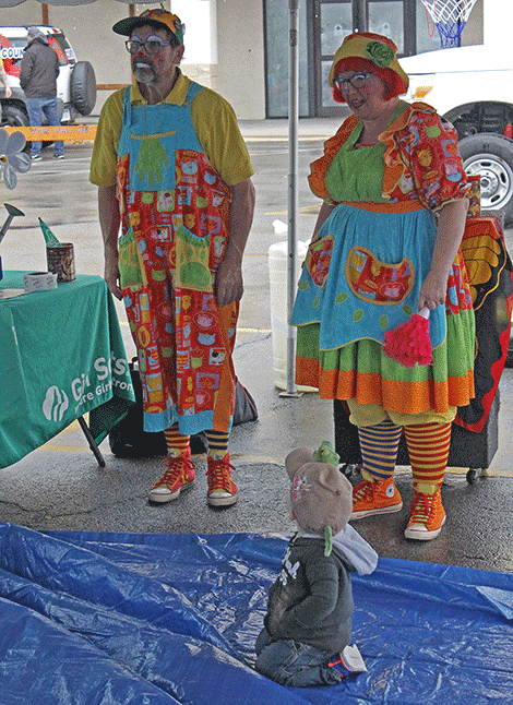 A youngster watches Cubby T. Clown and Friends as they get ready to start their show at Outer Market Mania on Friday.