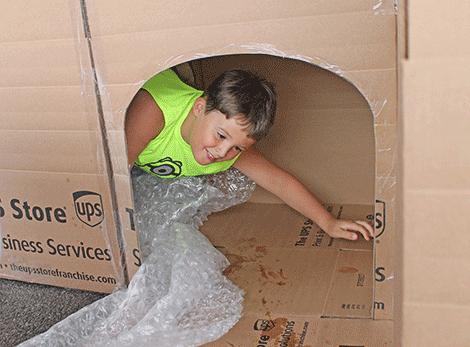 Matthew Rockefeller of Potsdam crawls through a box maze at Outer Market Mania on Friday.