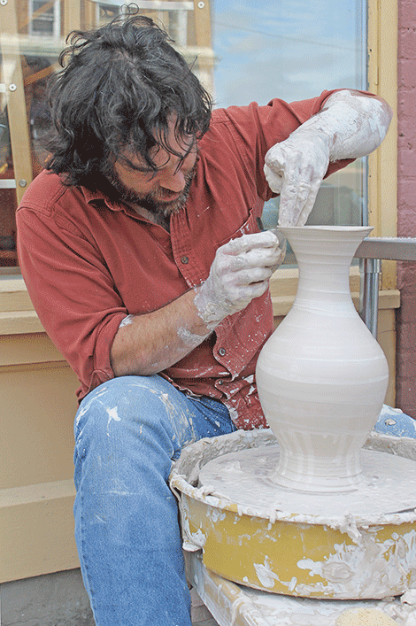 Isaac Jude makes pottery on Market Street on Thursday.