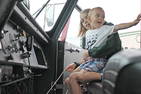 Parishville siblings Bailey Warren and Luke Sweeney check out the inside of a firetruck at Outer Market Mania on Friday.