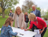 Potsdam-rally-pink-woman-signing.png
