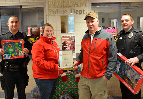Christina Reynolds gives Ronald Page with the Toys for Tots Commander's Award for donating $2,500 worth of toys. They are with recruit Jerrid Lavoie, left, and officer Kyle Fink.